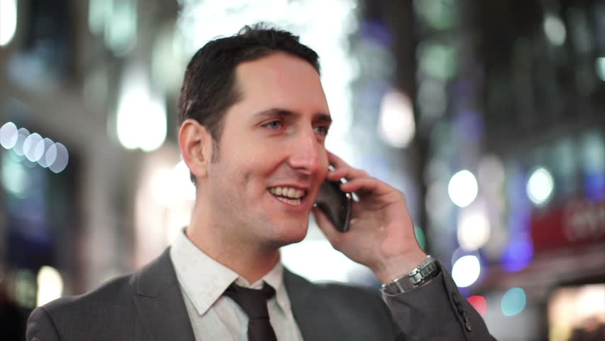 Portrait of smart cheerful businessman having a phone conversation on a London city street in the evening | Shutterstock HD Video #10250282