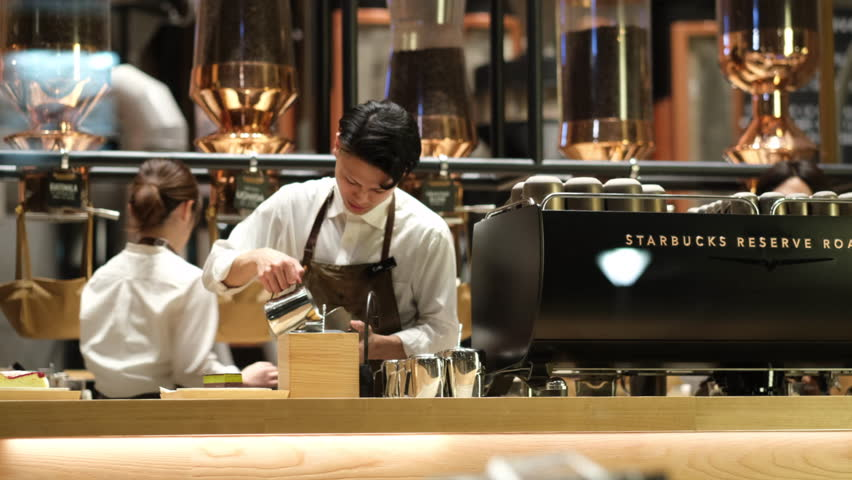 TOKYO, JAPAN - MARCH 2ND, 2019. Starbucks Reserve Roastery customers and baristas at night. The newly opened establishment is the 5th of such outlet and the largest in the world.