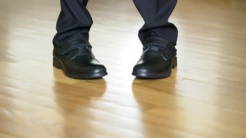 Legs of a man in black shoes dancing elements of dubstep on the brown floor background. View shot looking straight at the shoes and legs in black trousers.