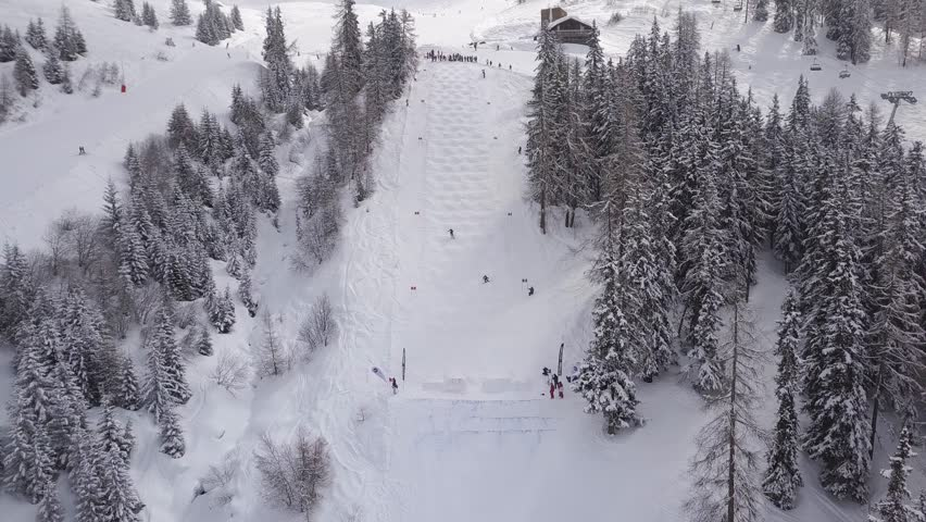 Aerial drone shot over two skiers racing down the white snowy slopes of Verbier, Switzerland. | Shutterstock HD Video #1025042858