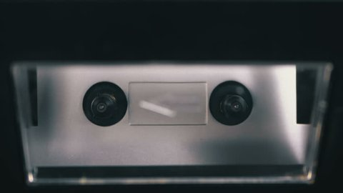 Audio Cassette is inserted into the Deck of the Audio Tape Recorder Playing and Rotates. Macro. Vintage transparent audio cassette tape with a blank label used for sound recording in a retro cassette