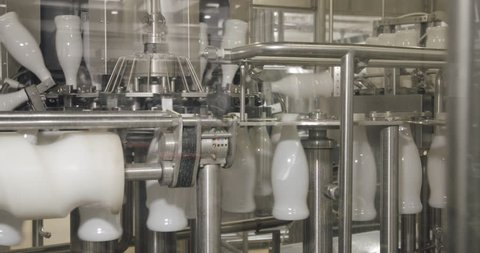 Milk production, white plastic bottles transported on conveyor, automated production line.