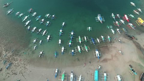 Aerial drone view of boats anchored in the bay with clear and turquoise water. Boat and yacht in the tropical lagoon. Tropical landscape. El Nido, Palawan island, Philippines.