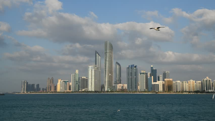 Abu Dhabi skyline. Birds flying. Yachts on the gulf. Golden hour clouds. Travel inspiration.  | Shutterstock HD Video #1025197658