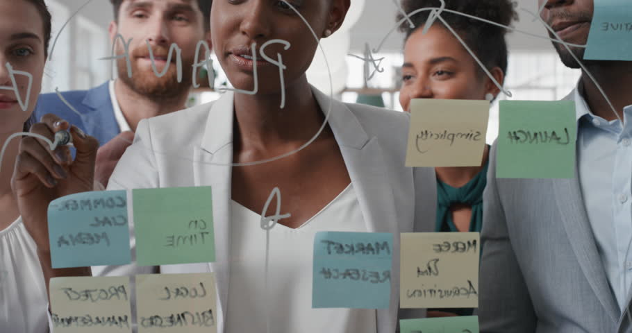 Corporate business people using sticky notes brainstorming problem solving strategy on glass whiteboard team leader woman showing solution for project deadline in office meeting | Shutterstock HD Video #1025208728