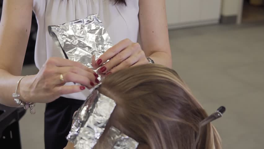 Hair stylist applying hair coloring dye to lighten up hair tone. Hairdresser makes coloring hair roots | Shutterstock HD Video #1025237768