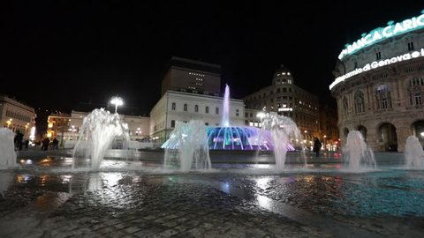 GENOA, ITALY - 03/02/2019: The monumental fountain of Piazza De Ferrari in Genoa, seen in the evening with its colored jets and people walking