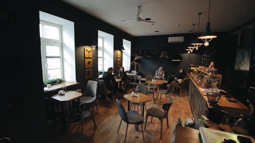 Minsk, Belarus - 11 January 2019: Candid image of young couple in a coffee shop. Caucasian man and woman sitting with a dog in a cafe. Long shot of loft style coffee shops.