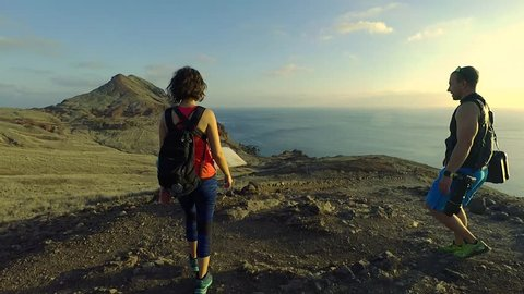 Happy couple of tourists is hiking on Madeira island. Exploring map, backside view. Full HD footage.