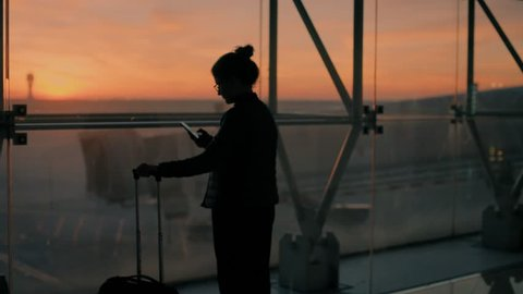 Blurred and unrecognizable young female traveler, leisure or business stands near glass window of big international airport hub with suitcase, scrolls through smartphone application,sunrise background