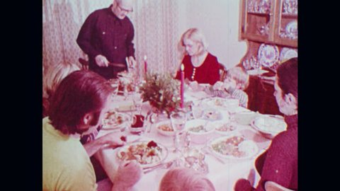 1970s: People sit around table, eat dinner. Child touches holly berries. Holly plant with berries. Jerusalem cherry plant.