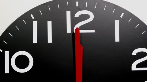 Close POV forward dolly shot of a large isolated black clock with red hands and white arabic numerals, zooming in on 12 o'clock.