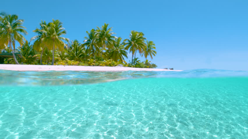 SLOW MOTION HALF IN HALF OUT: Stunning shot of the calm ocean surface and the idyllic tropical island sandy beach with lush palm trees towering into the clear blue sky. Picturesque One Foot Island. | Shutterstock HD Video #1025405558