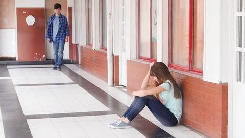 Asian girl sad seated on school hallway, caucasian boy supporting her, teenager bullying concept.