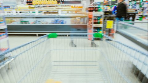 Time Lapse of the Shopping Cart Moving Between Various Aisles and Section in the Big Supermarket. Inside Trolley Various Healthy Items and Convenience Food.