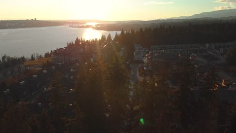 A townhouse complex at the edge of an evergreen forest in North Vancouver, BC, Canada at sunset.
