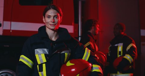Portrait of the young beautiful Caucasian woman fire fighter with a helmet in hand turning her head to the camera and smiling while standing in front of the big red car and her male colleagues