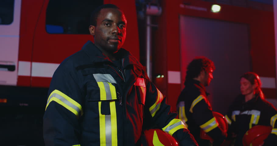 Portrait shot of the young African American man fire fighter turning his head to the camera and smiling while standing in front of the big red car and colleagues who talking. Indoor.