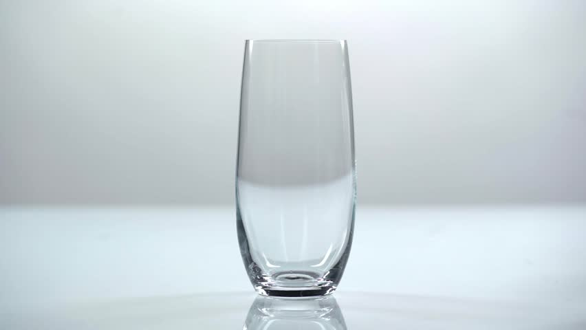 Studio shoot of water pouring into transparent glass on white background | Shutterstock HD Video #1025544518