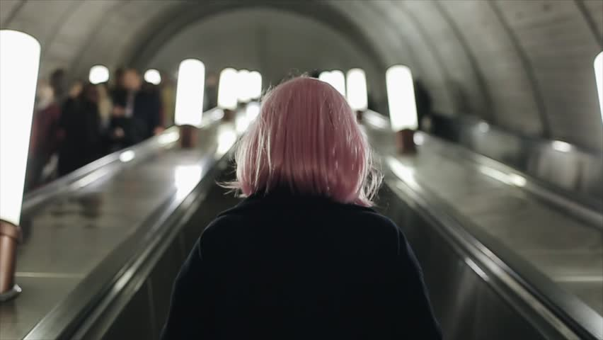 Back view of woman with pink hair using escalator in metro. | Shutterstock HD Video #1025551688