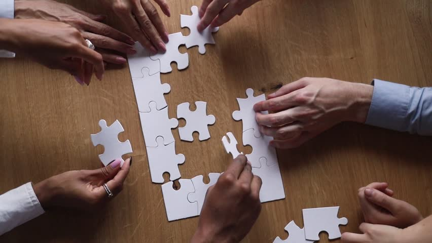Hands of diverse business team people collaborate assemble puzzle together connect pieces at desk find common purpose solution engaged in help support contribute in teamwork concept top close up view