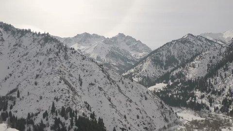 Winter aerial flight over the mountain landscape near Almaty city, Kazakhstan
