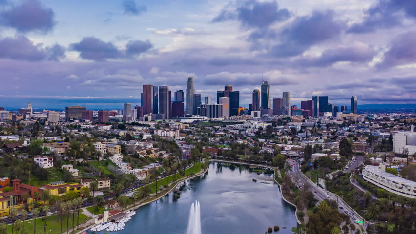 Cinematic urban aerial time lapse of downtown Los Angeles skyline with freeway traffic at dusk on a cloudy day | Shutterstock HD Video #1025666498