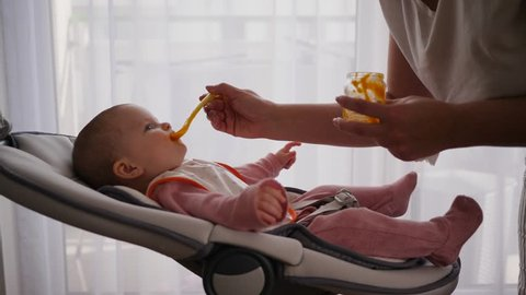 Mother leans to the child that lie in baby swing and feed with first food