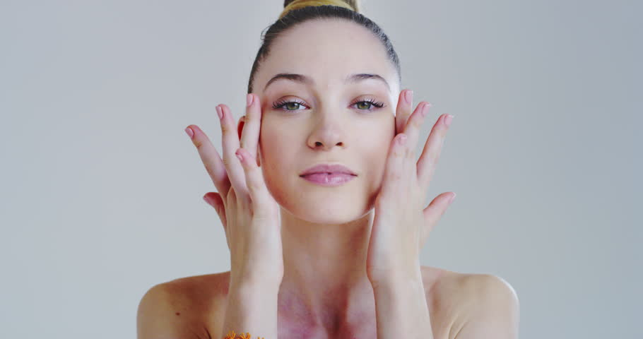 Slow motion of woman with beautiful face and perfect skin just cleaned from impurities pampering it gently with fingers to prepare for day or night cream.  | Shutterstock HD Video #1025721338