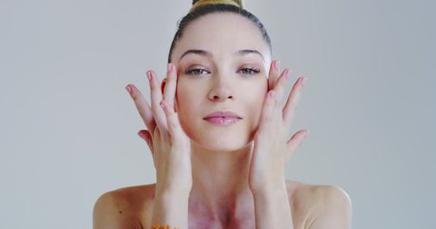 Slow motion of woman with beautiful face and perfect skin just cleaned from impurities pampering it gently with fingers to prepare for day or night cream.