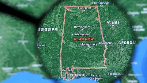 MIAMI BEACH. FLORIDA. USA - MARCH 2019: USA, Alabama on the political map. Alabama Borders. Alabama state under magnifying glass. Alabama Geography in the USA