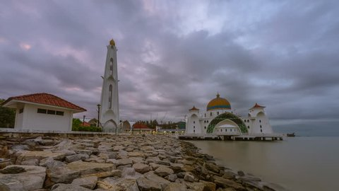 Dramatic Stormy Time lapse of sunrise and fast clouds at a mosque in Melaka, Malaysia at night to day. Pan up motion timelapse