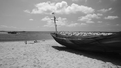 Thai fishing boat with blowing Thai flag on the beach shoot with beautiful blue cloudy sky (black and white/monochrome)