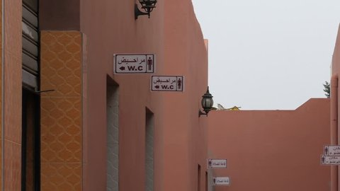Red brown color public toilet entrance with WC sign on wall in Morocco, Africa