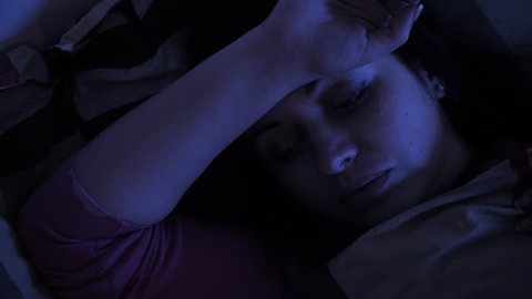 Woman has insomnia, thinking about her problems, can not sleep. Deep night