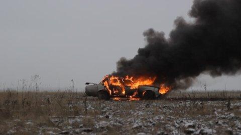 Car on fire on the field. Sedan car. Side view