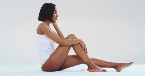 Slow motion of young dark skin woman with perfect body touching gently her hairless soft and silky legs after depilation isolated on a white background. Shot in 8K.