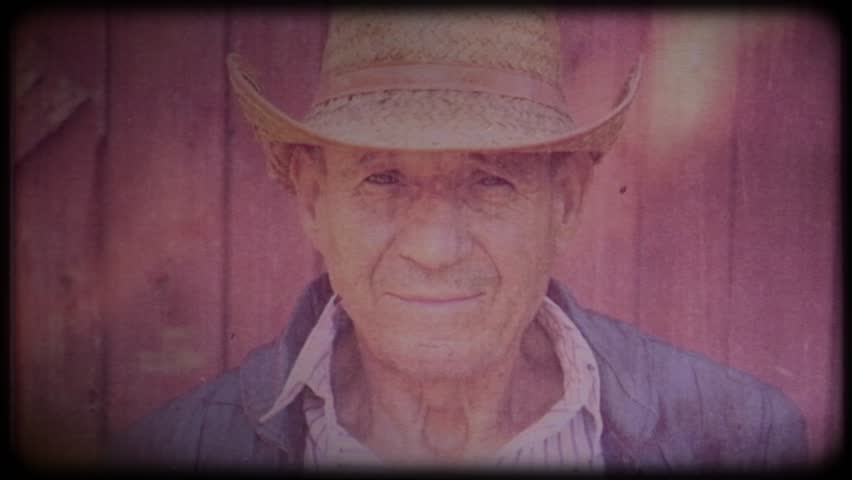 Old farmer in a straw hat near the farm. Portrait of an elderly man. Retiree. Video archive. Retro. Vintage. Farm animals. Raising animals for meat. Agriculture. Organic food. Ranch | Shutterstock HD Video #1025821778