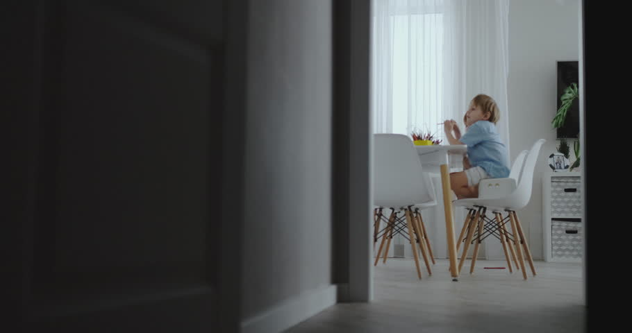 Happy family young beautiful mother and two sons draw with colored pencils sitting at the table in the kitchen. The camera moves in slow motion | Shutterstock HD Video #1025823968