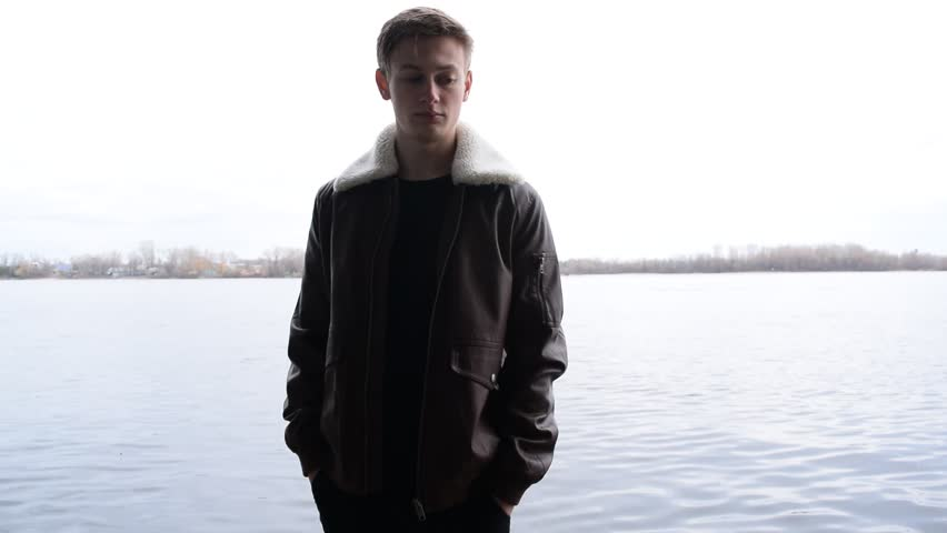 A young man in a leather jacket stands near the river in the city  #1025841308