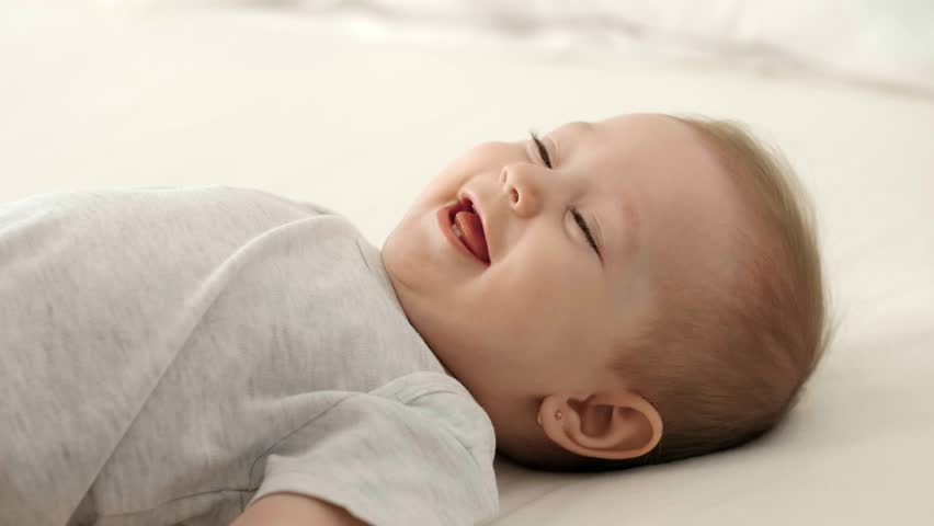 Loving mother tickling her baby girl on the bed | Shutterstock HD Video #1025844278