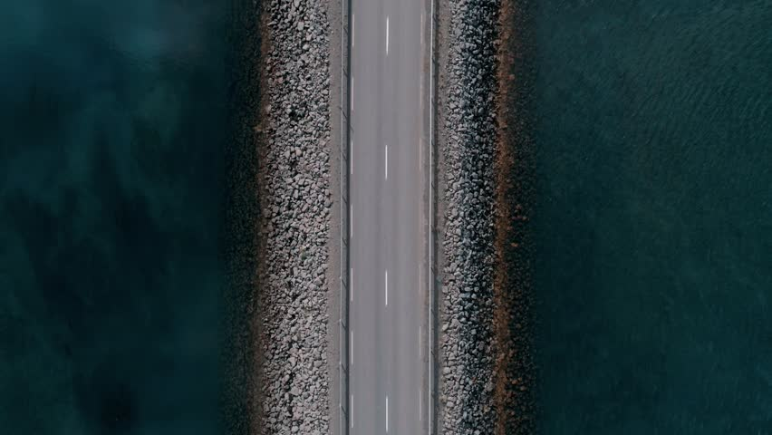 Straight down drone footage of bridge or road in middle of canal or lake separating sea from sweet water. Commuter or tourist traffic vehicles and cars drive by. Icelandic landscape | Shutterstock HD Video #1025858708