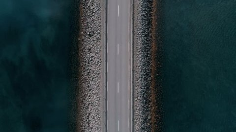 Straight down drone footage of bridge or road in middle of canal or lake separating sea from sweet water. Commuter or tourist traffic vehicles and cars drive by. Icelandic landscape
