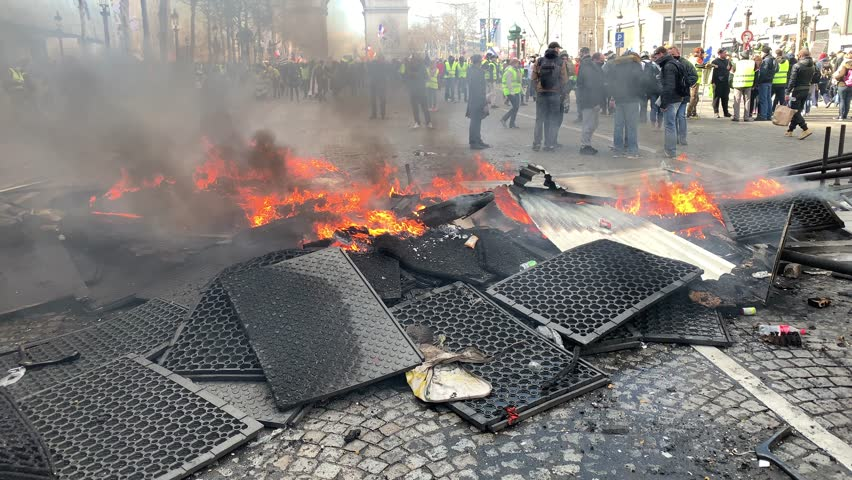 """Paris, FRANCE - March, 16 2019 : Urban furnitures burning during a demonstration of yellow vests """"Gilets Jaunes"""" at Paris on Champs Elysees."""