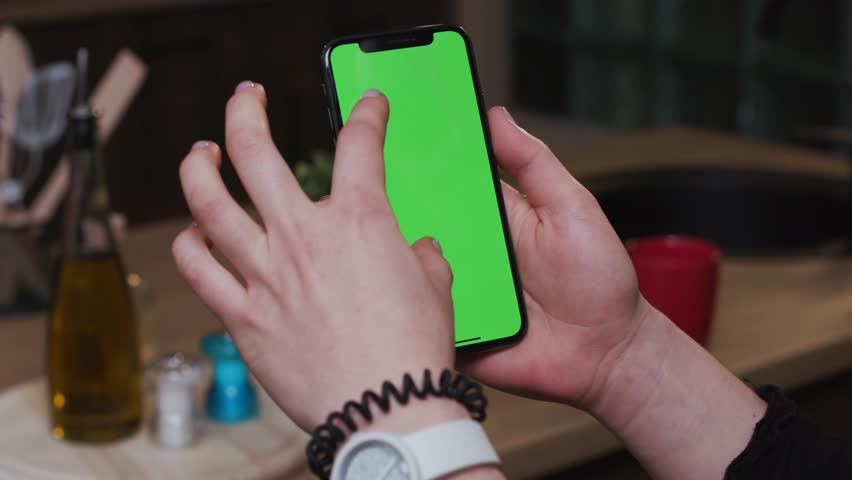 Tokio, Japan - April 7, 2018: Close up woman hand hold smartphone with vertical green screen on kitchen at home breakfast browse food girl house shopping internet abstract slow motion | Shutterstock HD Video #1025899418