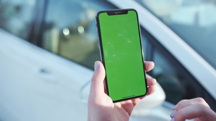 Lviv, Ukraine - May 19, 2018: Girl use phone with vertical green screen in the background white car woman chroma key technology use mobile internet message smart sunset cell slow motion | Shutterstock HD Video #1025899448