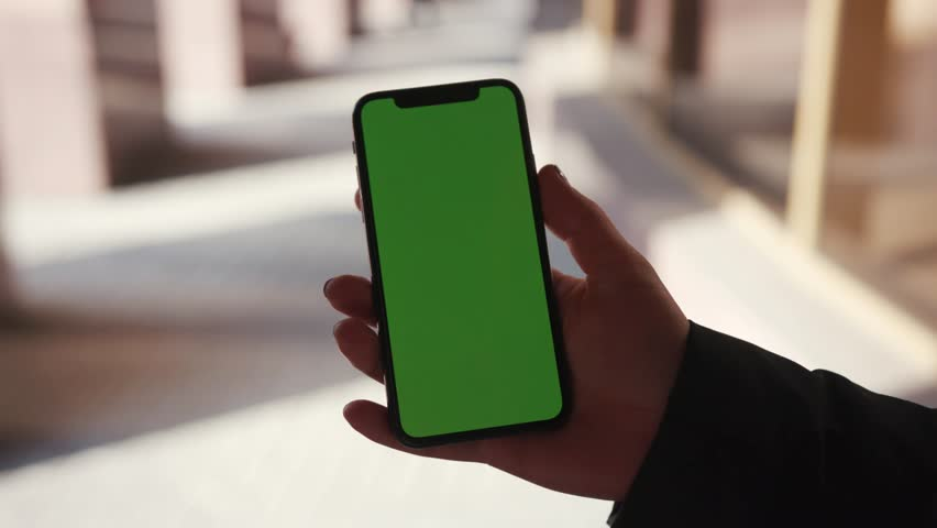 Lviv, Ukraine - May 19, 2018: Young woman hands holding phone with horizontal green screen on city street background sunset people car busy finger touch message cellphone display girl slow motion | Shutterstock HD Video #1025899478
