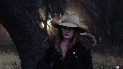 A female hunter holding a weapon, looking around in the cold forest forement, slow motion 23.98 fps.