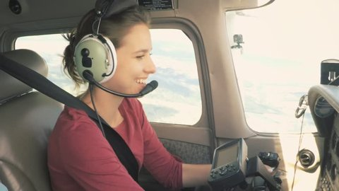 Young happy woman piloting a civil aircraft talking on intercom and smiling