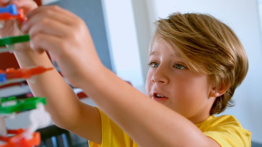 Side view of cute Caucasian schoolboy studying DNA model in classroom at school. He is assembling DNA model 4k | Shutterstock HD Video #1025908328